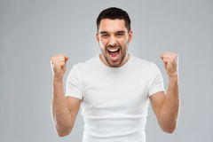 Young man celebrating victory over gray Stock Photo