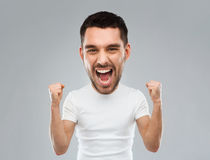 Young man celebrating victory over gray. Emotion, success, gesture and people concept - young man celebrating victory and screaming over gray background  (funny Stock Image
