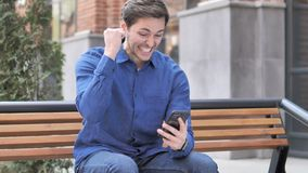 Young Man Celebrating Win on Smartphone, Sitting Outdoor on Bench. 4k high quality, 4k high quality stock video footage