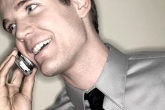Young Man on Cell phone. Young man in a shirt and tie, chats on the cell phone, looking away with a smile - ring flash stock photo