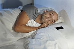Young man cell phone addict in bed at night sleeping happy together with mobile phone Stock Image