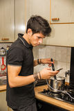 Young Man with Cell Phone Cooking Food on Stove. Distracted Young Man with Dark Hair Stirring Pot of Food on Kitchen Stove Top While Looking at Cell Phone Screen stock photos