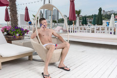 Young Man with Cell Phone on Deck of Luxury Resort Royalty Free Stock Image