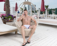 Young Man with Cell Phone on Deck of Luxury Resort Royalty Free Stock Photo