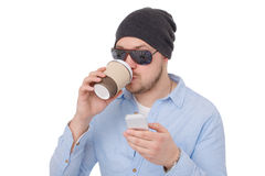 Young man with the cell phone. Young handsome man with the cell phone and cup of coffee on white background Royalty Free Stock Images
