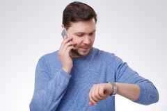 Young man with the cell phone. Looking on his watch Royalty Free Stock Images