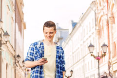 Young man with cell phone on the street. During summer vacation time in Europe Stock Images