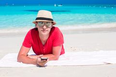 Young man with cell phone on tropical white beach Stock Images