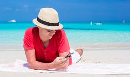 Young man with cell phone on tropical white beach Stock Photo
