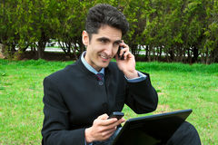 Young man with cell phones and laptop. Stock Images