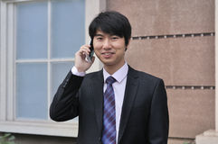 Young man on cellphone. Handsome chinese young man on cellphone,outdoors Royalty Free Stock Photo