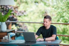 Young man with laptop in outdoor cafe drinking coffee. Man using mobile smartphone. Stock Photography