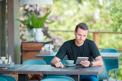 Young man with laptop in outdoor cafe drinking coffee. Man using mobile smartphone. Young man with cellphone outdoors in outdoor cafe. Man using mobile Royalty Free Stock Images