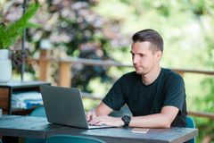 Young man with laptop in outdoor cafe drinking coffee. Man using mobile smartphone. Young man with cellphone outdoors in outdoor cafe. Man using mobile Stock Image