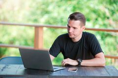 Young man with cellphone outdoors in outdoor cafe. Man using mobile smartphone. Young man with cellphone outdoors in outdoor cafe. Man using a laptop and a Royalty Free Stock Image