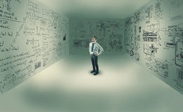 Young man in center of a room. Looking up, in a room with mathematical formulas written on wall royalty free stock photos