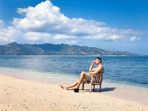 Young man in chair resting on the beach Stock Images