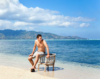 Young man in chair resting on the beach Stock Photography