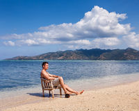 Young man in chair resting on the beach Royalty Free Stock Images