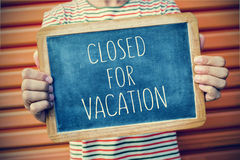 Young man with a chalkboard with the text closed for vacation, f Royalty Free Stock Photos