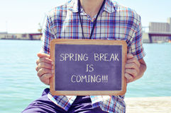 Young man with a chalkboard with the text spring break is coming. A young caucasian man sitting in a wooden pier shows a chalkboard with the text spring break is Stock Images