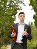 Young man with champagne and chocolates Stock Image