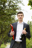 Young man with champagne and chocolates Royalty Free Stock Images