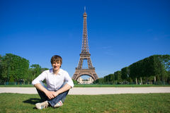 Young man on the Champs de Mars. With view of the Eiffel Tower Royalty Free Stock Image
