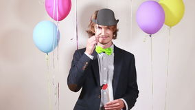 Young man changing props in photo booth stock video