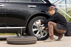 Young man changing the punctured tyre on his car royalty free stock photography