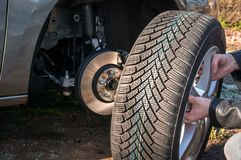 Man is changing summer car wheel, tire before winter. Young man is changing summer car wheel, tire before winter royalty free stock photo