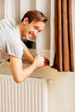 Young man changing temperature of radiator royalty free stock images