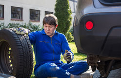 Young man changing wheel on car Stock Image
