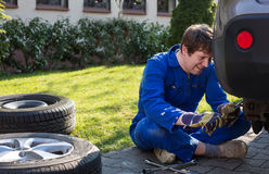 Young man changing wheel on car Royalty Free Stock Photography