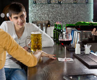Young man chatting to his girlfriend at the bar. Attractive young man chatting to his girlfriend over a beer at the bar smiling as he listens to her talking royalty free stock photo