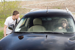 Young man chatting up a female driver Stock Images