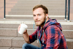 Young man in checkered shirt sitting on stairs and drinking coff Stock Photography