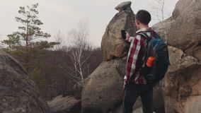 Young man in a checkered shirt stands on the top of the big rock and takes several shots of amazing scenery. No people stock video footage
