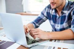Young man in checkered shirt using laptop at home Stock Image