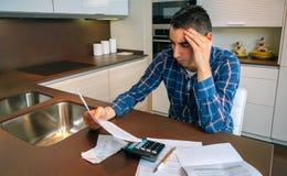 Young man checking bills Stock Photos
