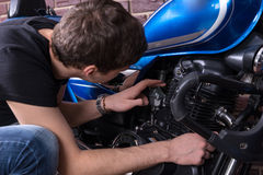 Young man checking his motorbike Stock Image