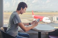 Young man checking his phone in the airport. Waiting the flight stock image