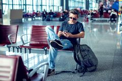 Young man checking his phone while waiting his flight in the air. Port at the departure area Stock Photo