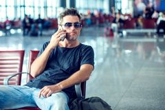 Young man checking his phone while waiting his flight in the air. Port at the departure area Royalty Free Stock Photos