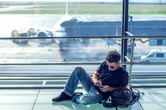 Young man checking his phone while waiting his flight in the air. Port. Travel concept Stock Photo