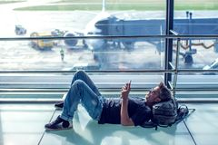 Young man checking his phone while waiting his flight in the air. Port. Travel concept Royalty Free Stock Photos