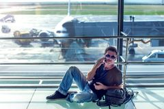 Young man checking his phone while waiting his flight in the air. Port. Travel concept Stock Images