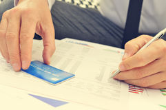 Young man checking the information of his credit card Royalty Free Stock Images
