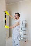 Young man checking level of house wall Stock Photo