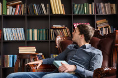 Young man checking out books in a library Royalty Free Stock Photos